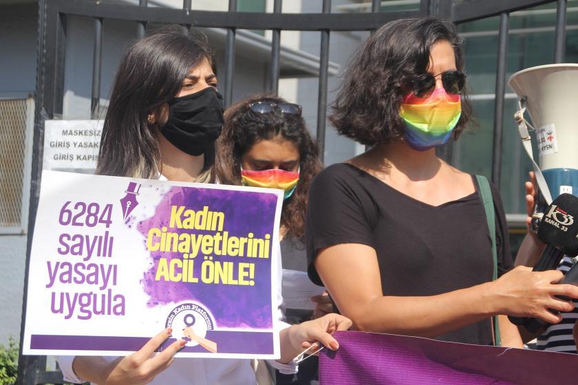 Kadın cinayetlerini önle yazılı bir döviz tutan yüzü maskeli kadın ve yanında megafon tutan bir kadın