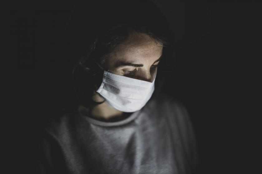 Yüzünde maske olan genç bir erkek.