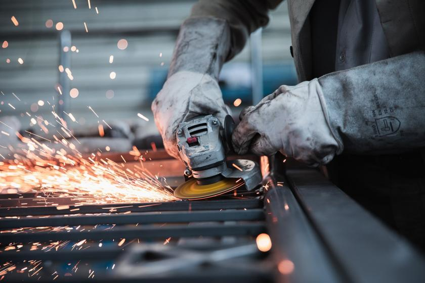 Fabrikada taşlama makinesiyle çalışan bir işçi.