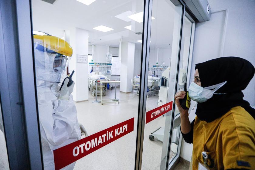 Yoğun bakım ünitesinin içerisinde olan sağlık çalışanı dışarıdaki çalışan ile telsiz vasıtası ile konuşurken.