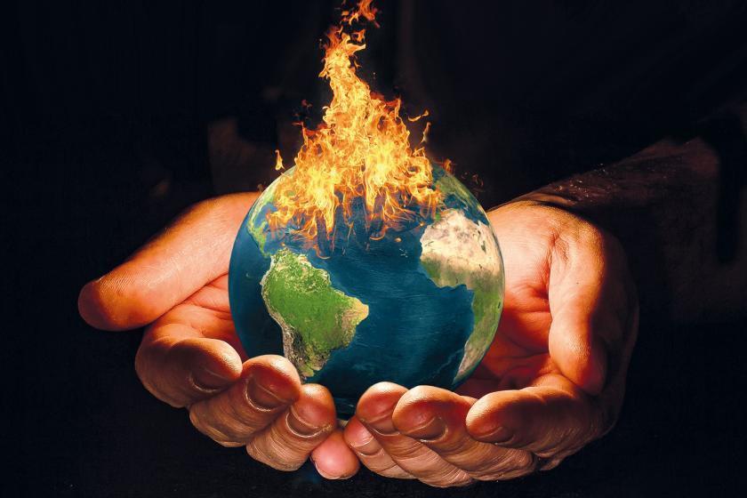 Bir kişinin elinde yanan dünya tasviri.