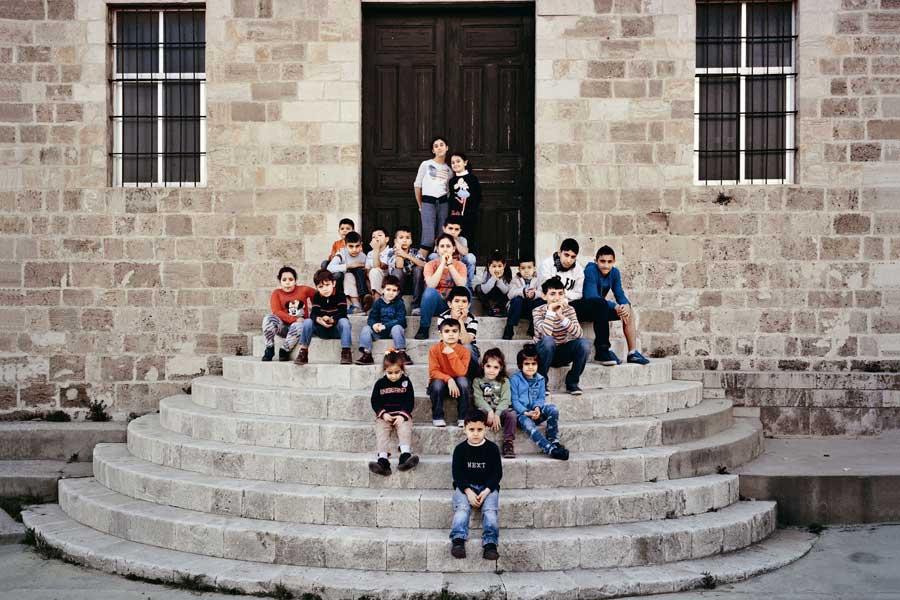 1915'in ardından hayatta kalan, ailelerini kaybetmiş çocukların Lübnan'da yerleştirildikleri ilk yer olan, Cübeyl'deki Birds Nest (Kuşların Yuvası) Yetimhanesi'nde çekilen bu fotoğrafın öyküsü de bir hayli ilginç. Arık, çocukların fotoğrafını çekmek için okul müdürüyle okulu gezmektedir. Önce bir sahne önünde bu toplu fotoğrafı çekmeyi düşünür. Fakat daha sonra bu merdivenleri görünce ilk fikrinden vazgeçtiğini söyler. Müdür nedenini sorduğunda ise 'Bilmem, çocukluğumu hatırlattı bana burası' der. Müdür de gülümseyerek 'Ama bu senin hikâyen değil, bizim hikâyemiz' diye yanıtlar ve daha sonra yıllar önce buradaki yetimlere annelik yapan Maria Jacobsen'in 1950'lerde çocuklarla birlikte aynı merdivende çekilmiş bir fotoğrafını gösterir.