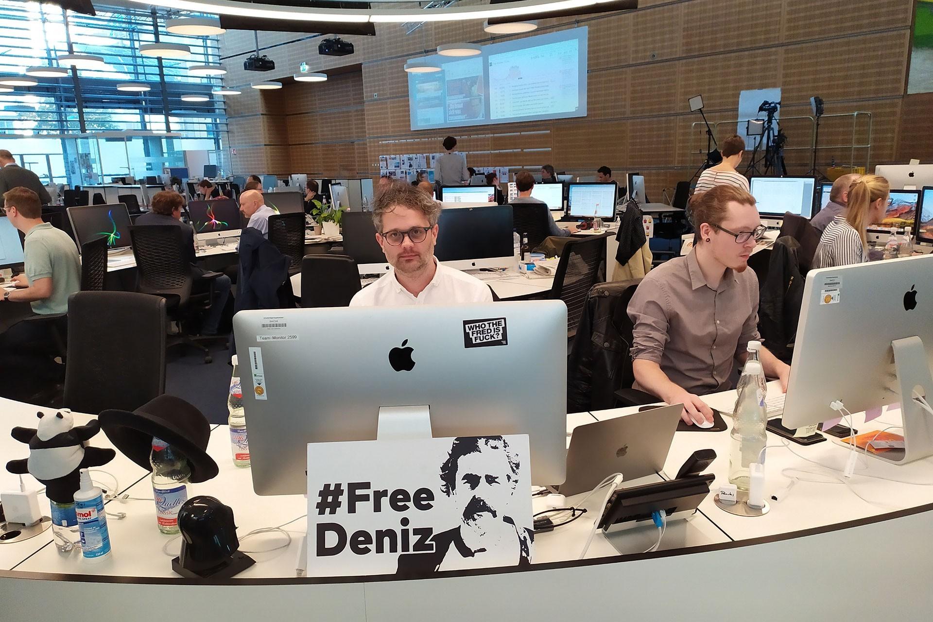 Die Welt'in Sosyal Medya Editörü Dominik Sindern'in, masasının önündeki #FreeDeniz yazılı görsel, Deniz'in bırakılmasının üzerinden 1 yıl 7 ay geçmiş olmasına rağmen duruyor