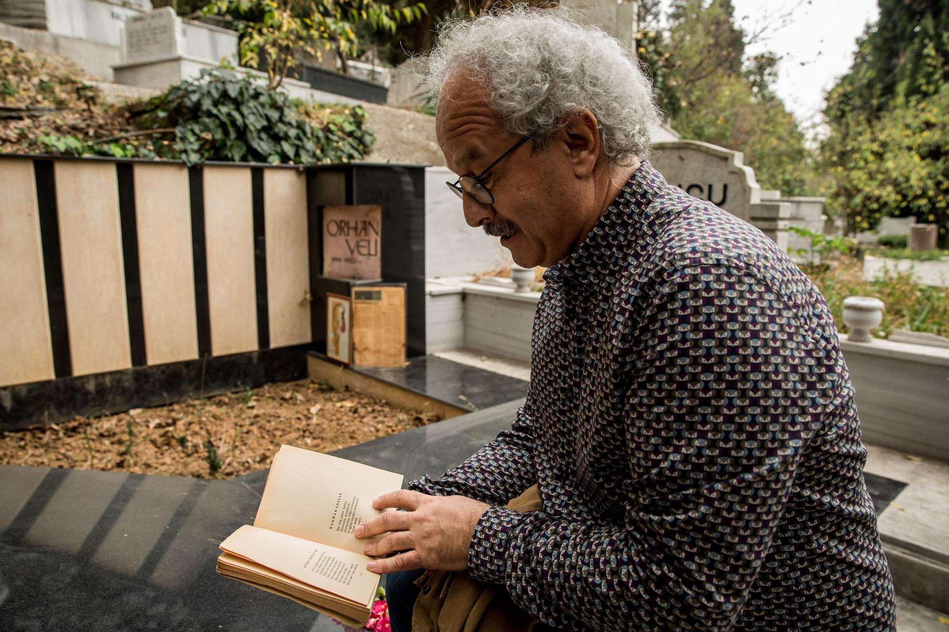 Şair Akgün Akova, Orhan Veli'nin mezarı başında şiir okuyor.
