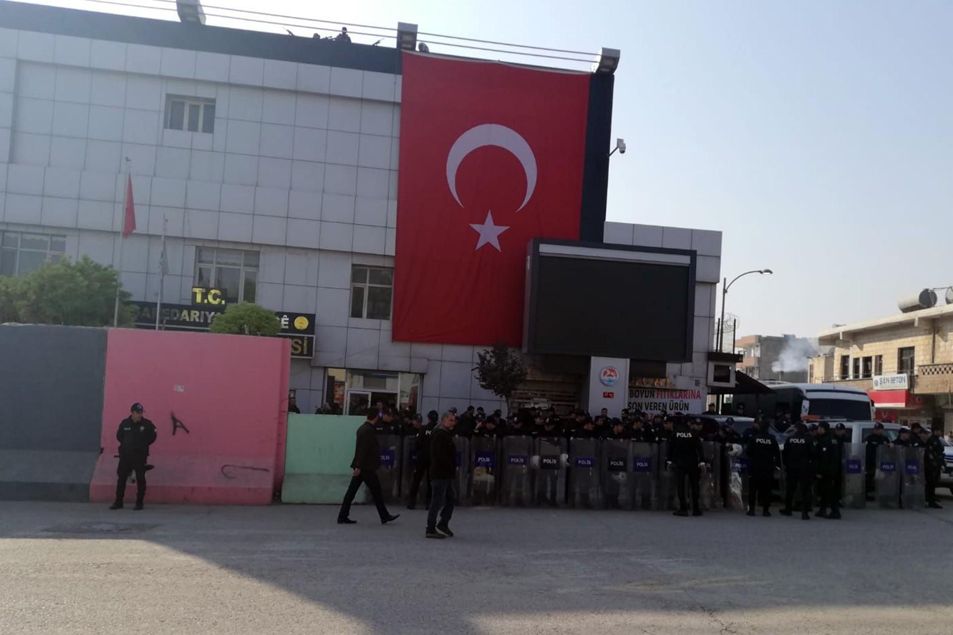 Suruç Belediyesi önünde barikat kuran polisler ve binaya asılan Türk bayrağı