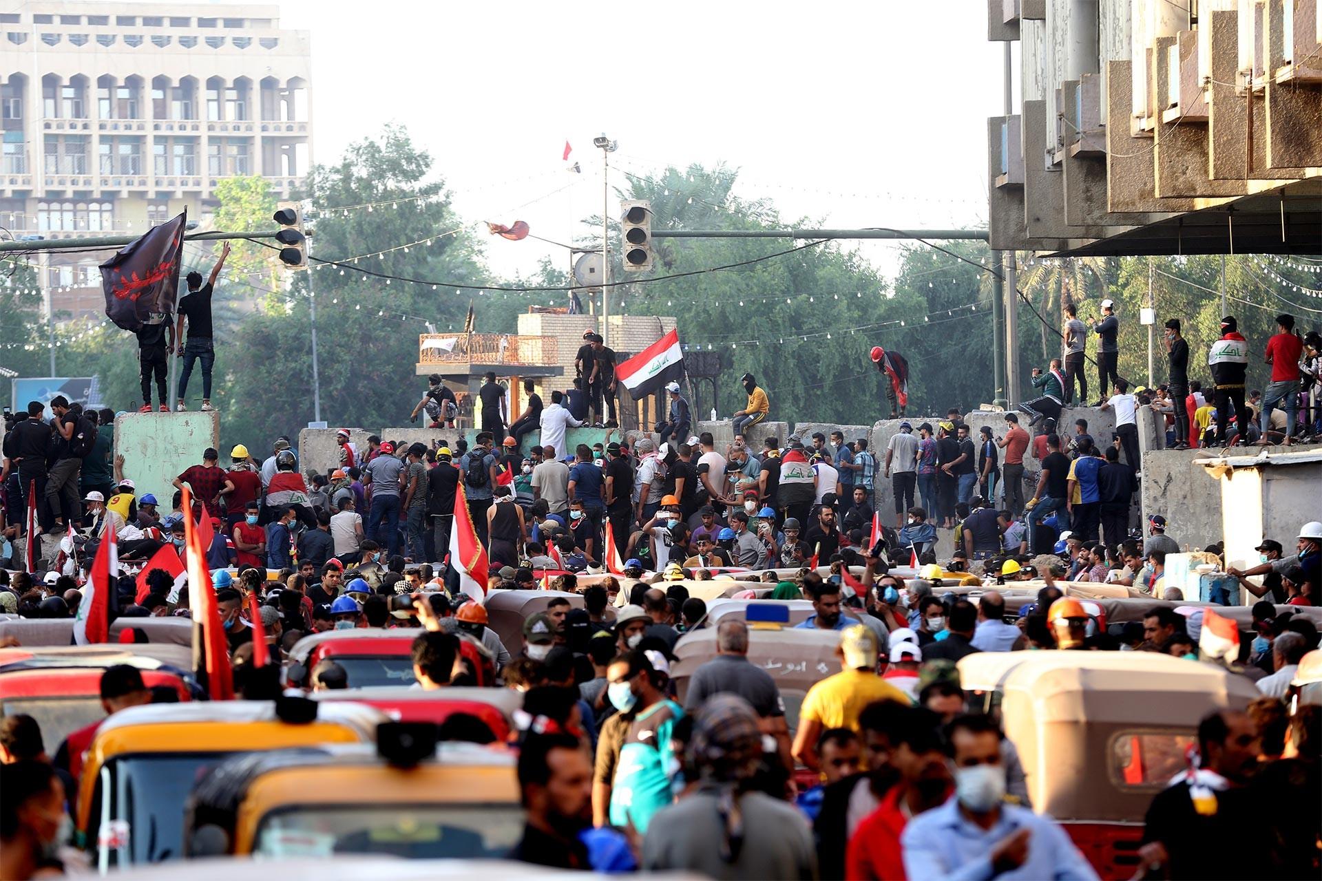 Bağdat'ta Yeşil Bölge girişine konulan beton bariyerler önünde hükümeti protesto eden Irak halkı