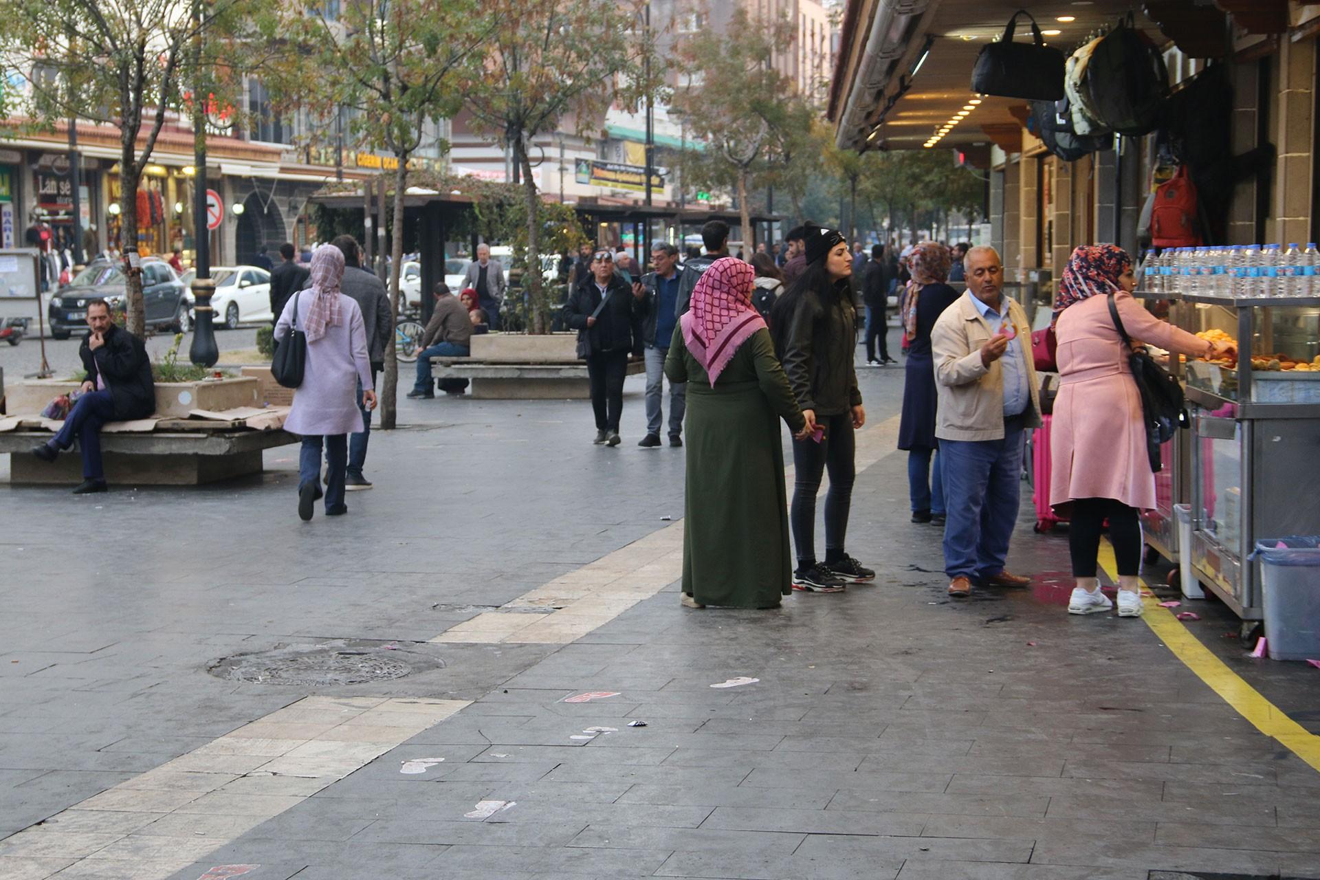 Diyarbakır'de caddede yürüyen, dükkanların önünde gündelik yaşantılarına devam eden yurttaşlar.