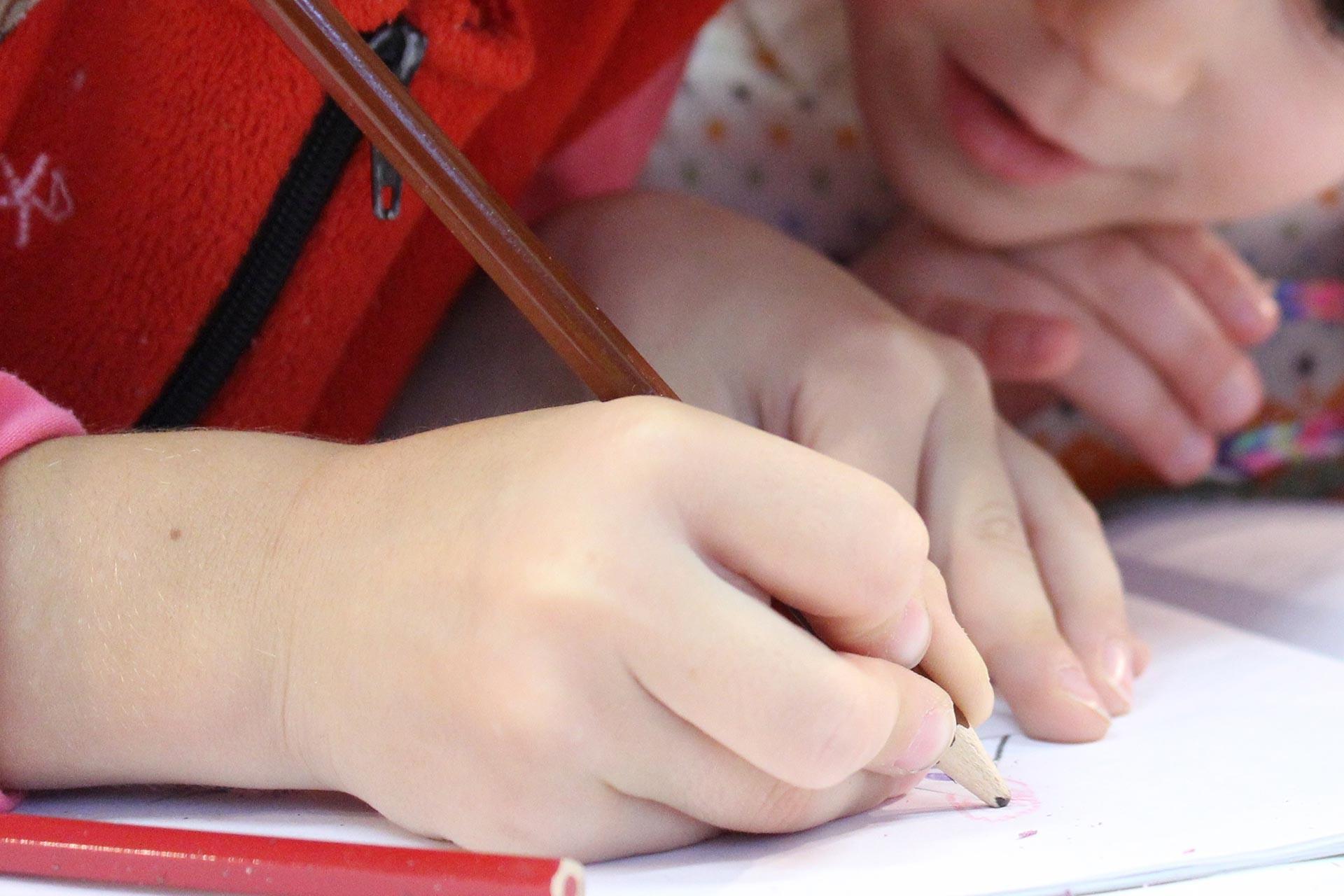 Kurşun kalemle deftere yazı yazan çocuklar