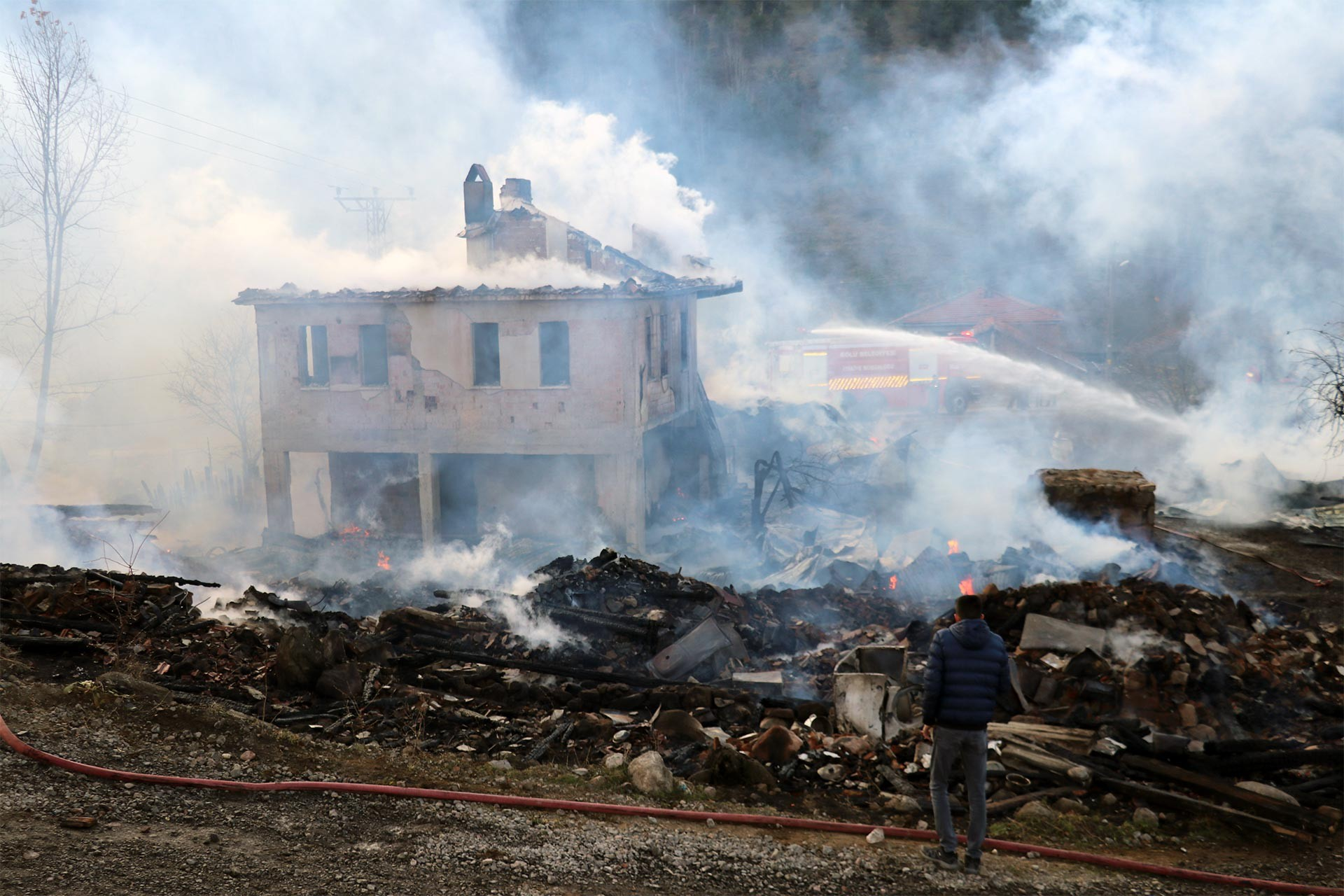 Yangın nedeniyle harap olan evlerden birinde sürdürülen soğutma çalışması