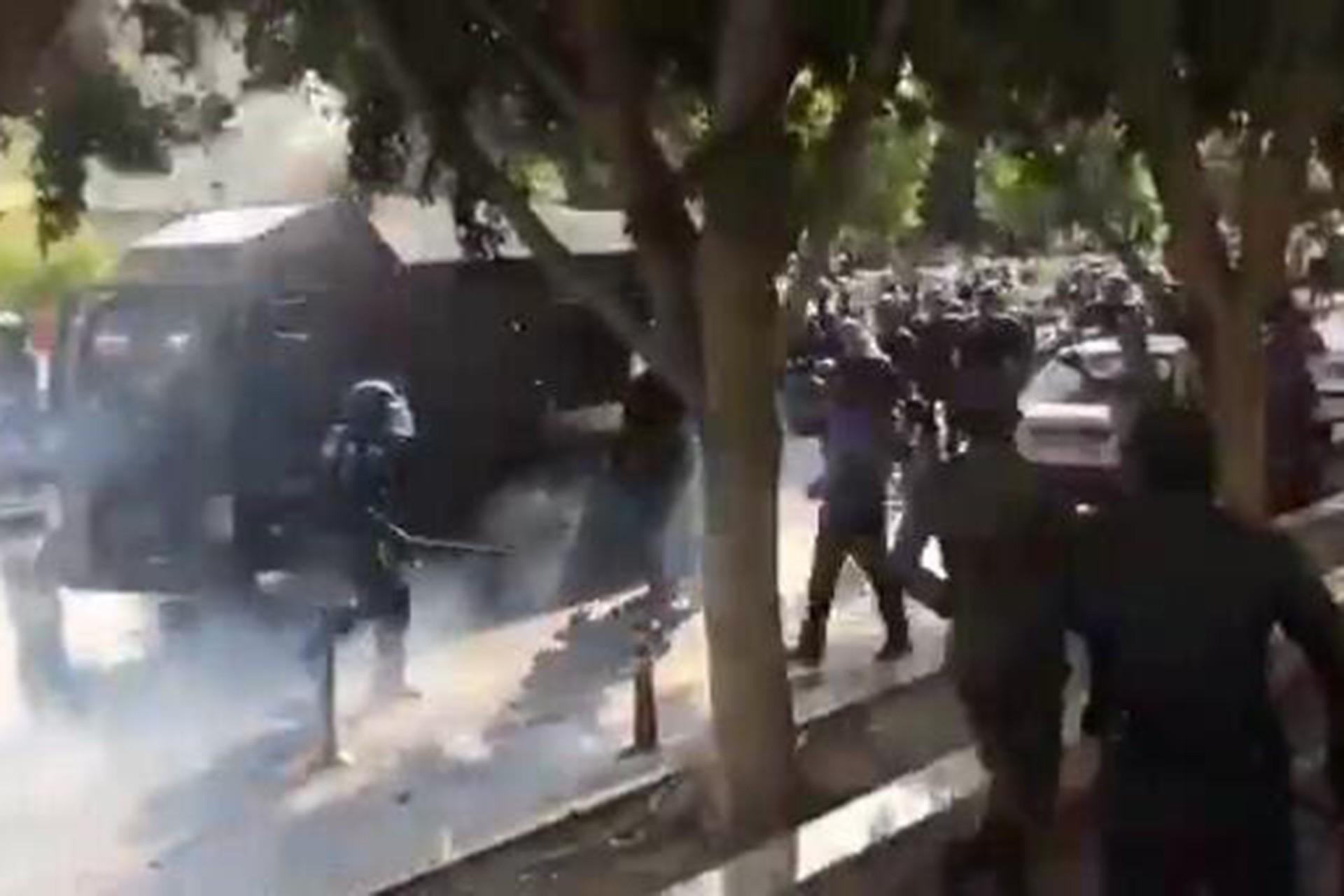 İran'daki protesto gösterileri sırasında polisin biber gazı ve cop kullandığı andan bir fotoğraf