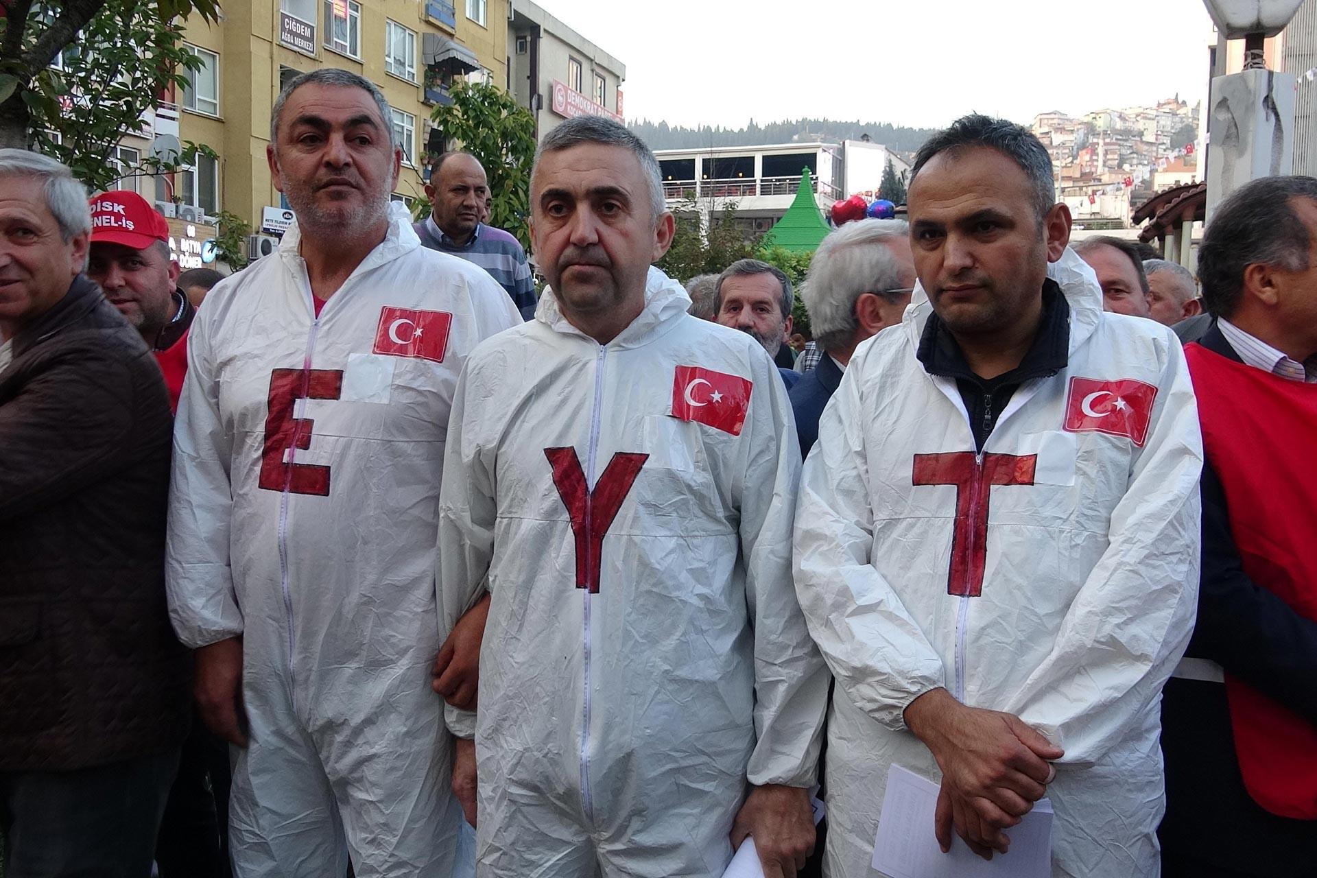 Basın açıklamasına katılan EYT mağduru üç kişi, üzerlerinde 'E', 'Y' ve 'T' harfleri bulunan tulumlarla yan yana dururken