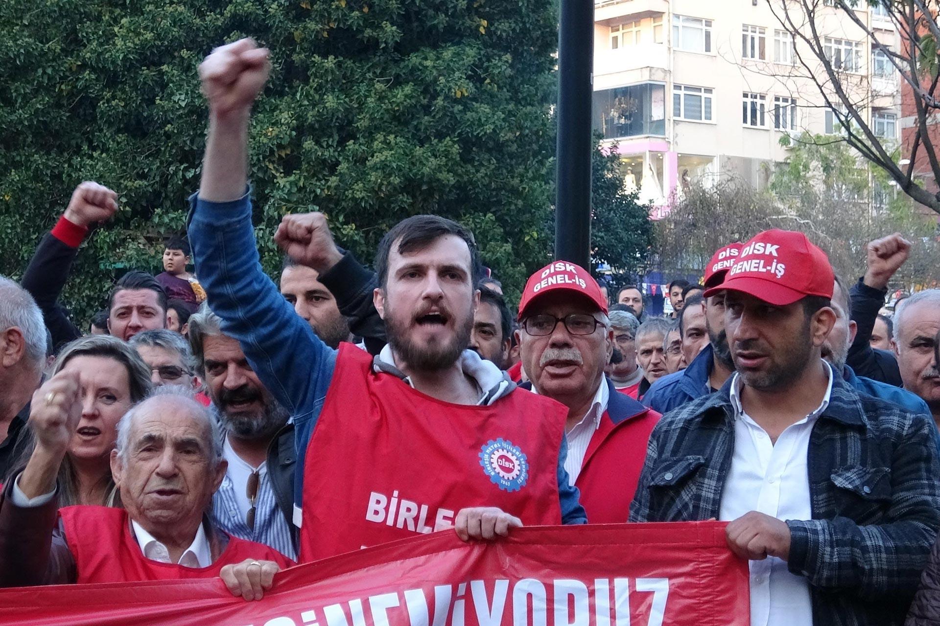 DİSK üyesi bir işçi basın açıklaması sırasında yumruğunu havaya kaldırarak slogan atarken