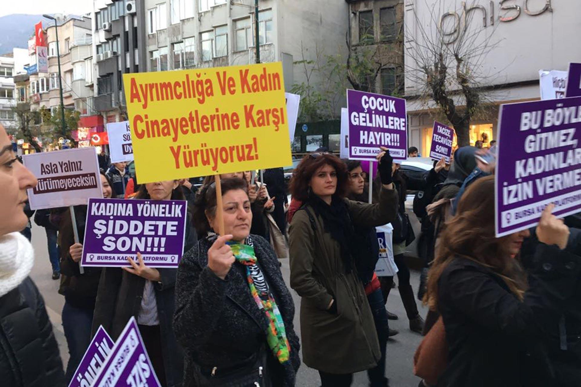 25 Kasım'da yapılan bir eylemde elinde 'Ayrımcılığa ve kadın cinayetlerine karşı yürüyoruz!' yazılı döviz tutan kadın