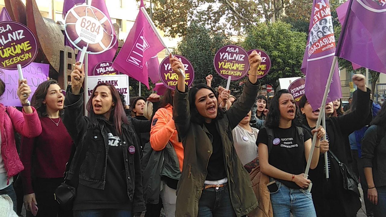Şiddete karşı dövizler ve mor bayraklar taşıyan genç kadınlar.