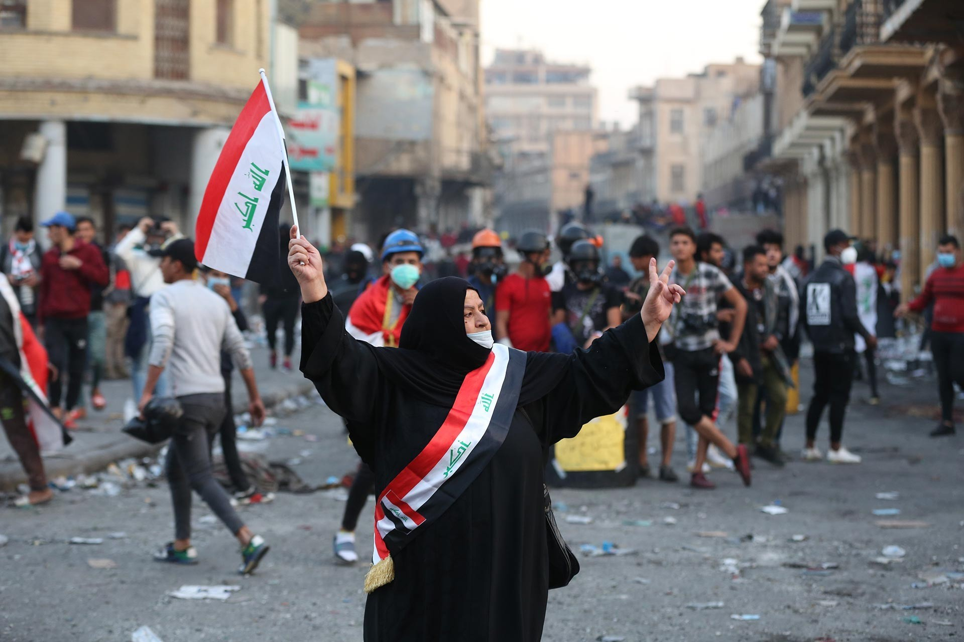 Woman protester holding a flag at her hand, in front of the crowd in Iraq.