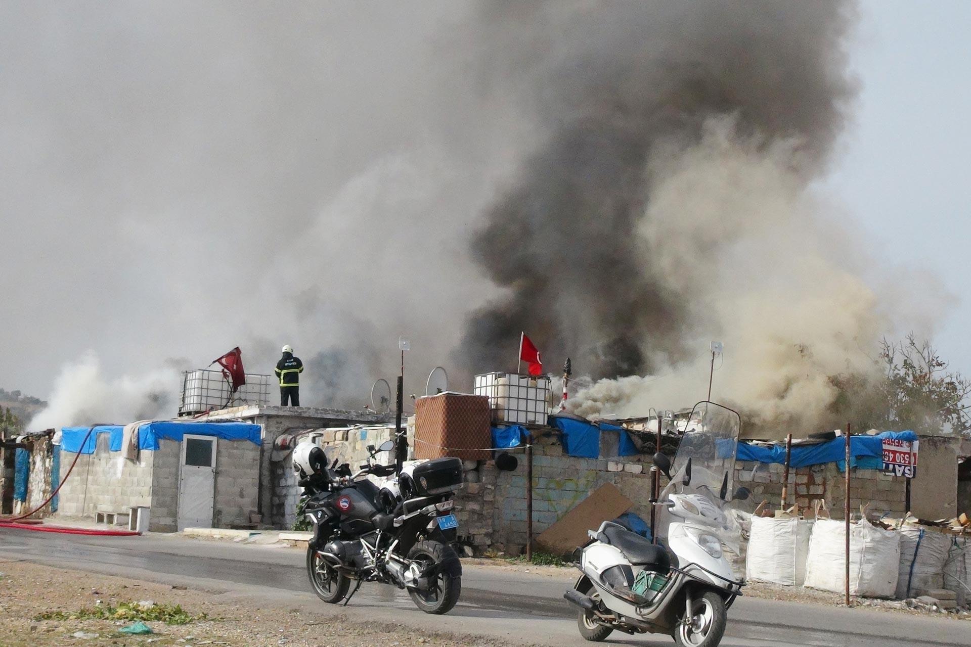 İtfaiye ekipleri barakada çıkan yangını söndürmeye çalışırken
