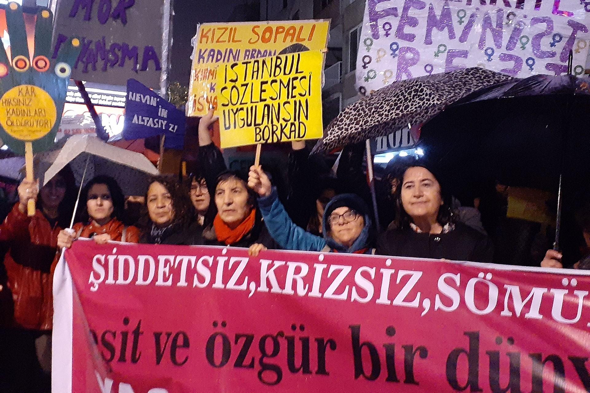 Kadınlar taleplerini anlatan pankart ve dövizlerle eylemde.