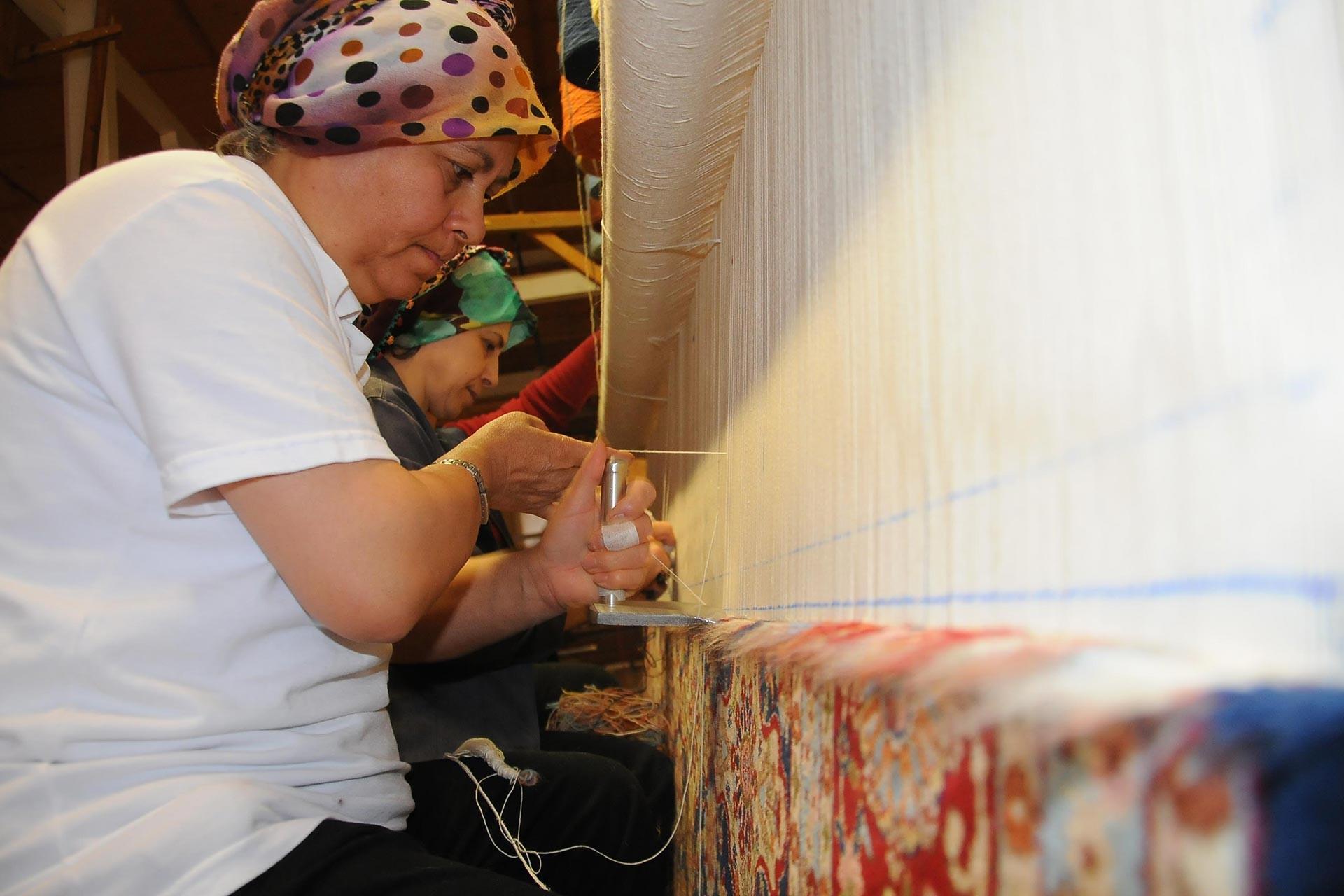 Halı tezgahında dokuma yapan kadın