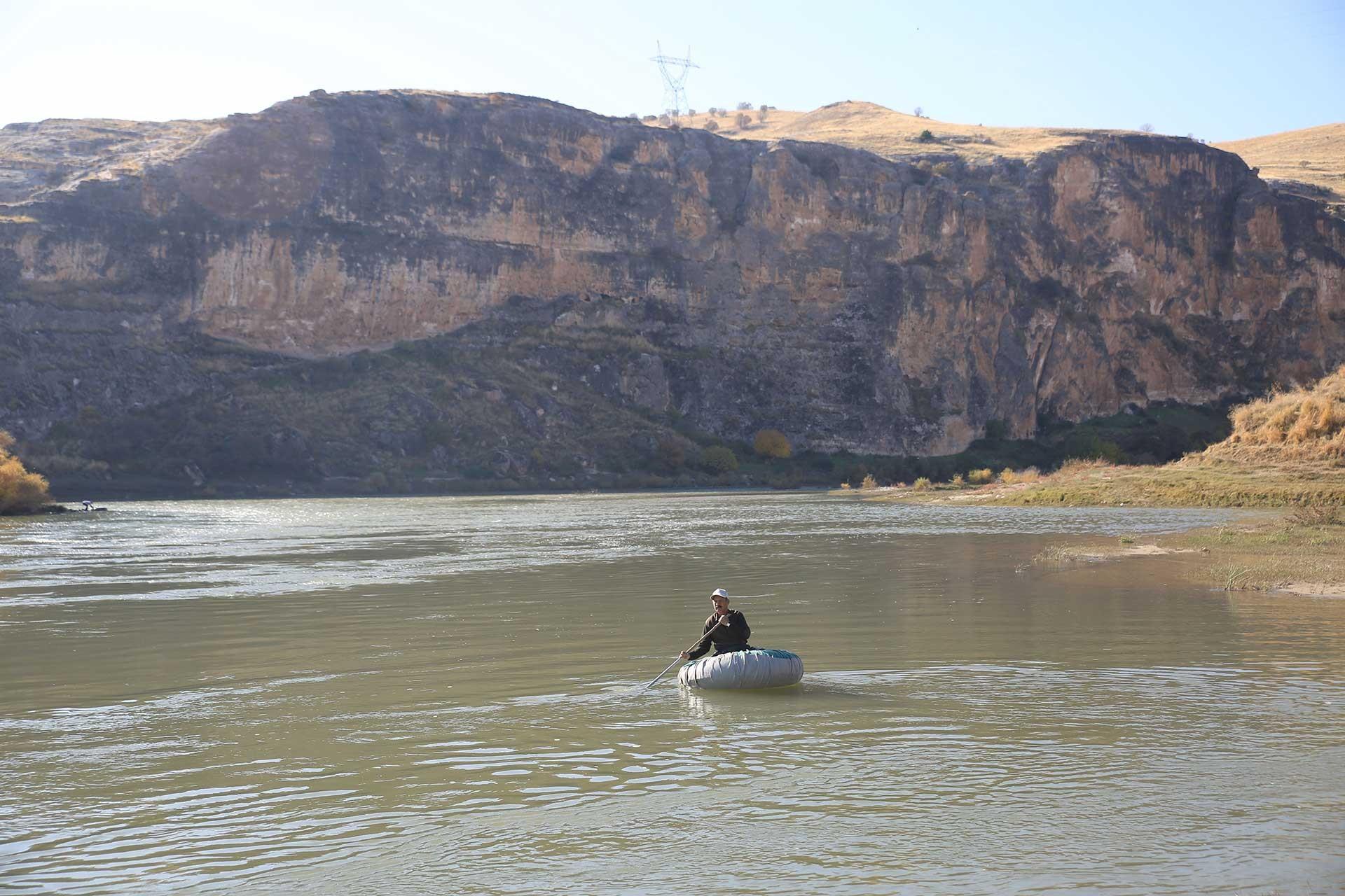 Dicle Nehrin'deki bir botta bir erkek kürek çekiyor.