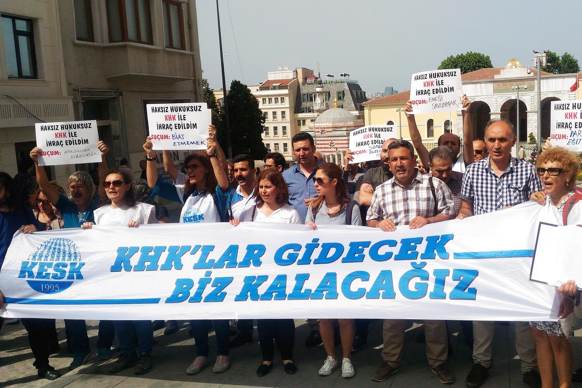 KESK üyesi emekçiler, 'KHK'lar gidecek biz kalacağız' yazılı pankart arkasında eylem yaparken