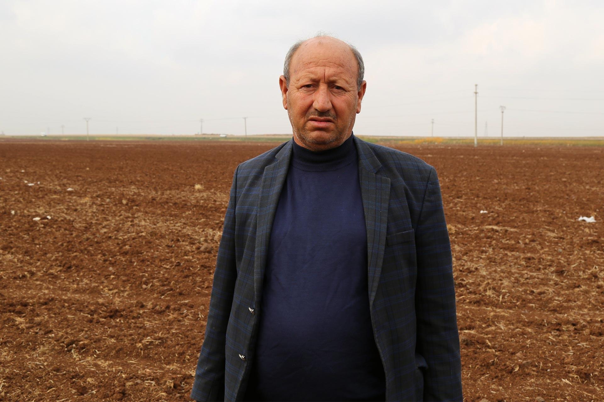 Tarlasının önünde poz veren çiftçi