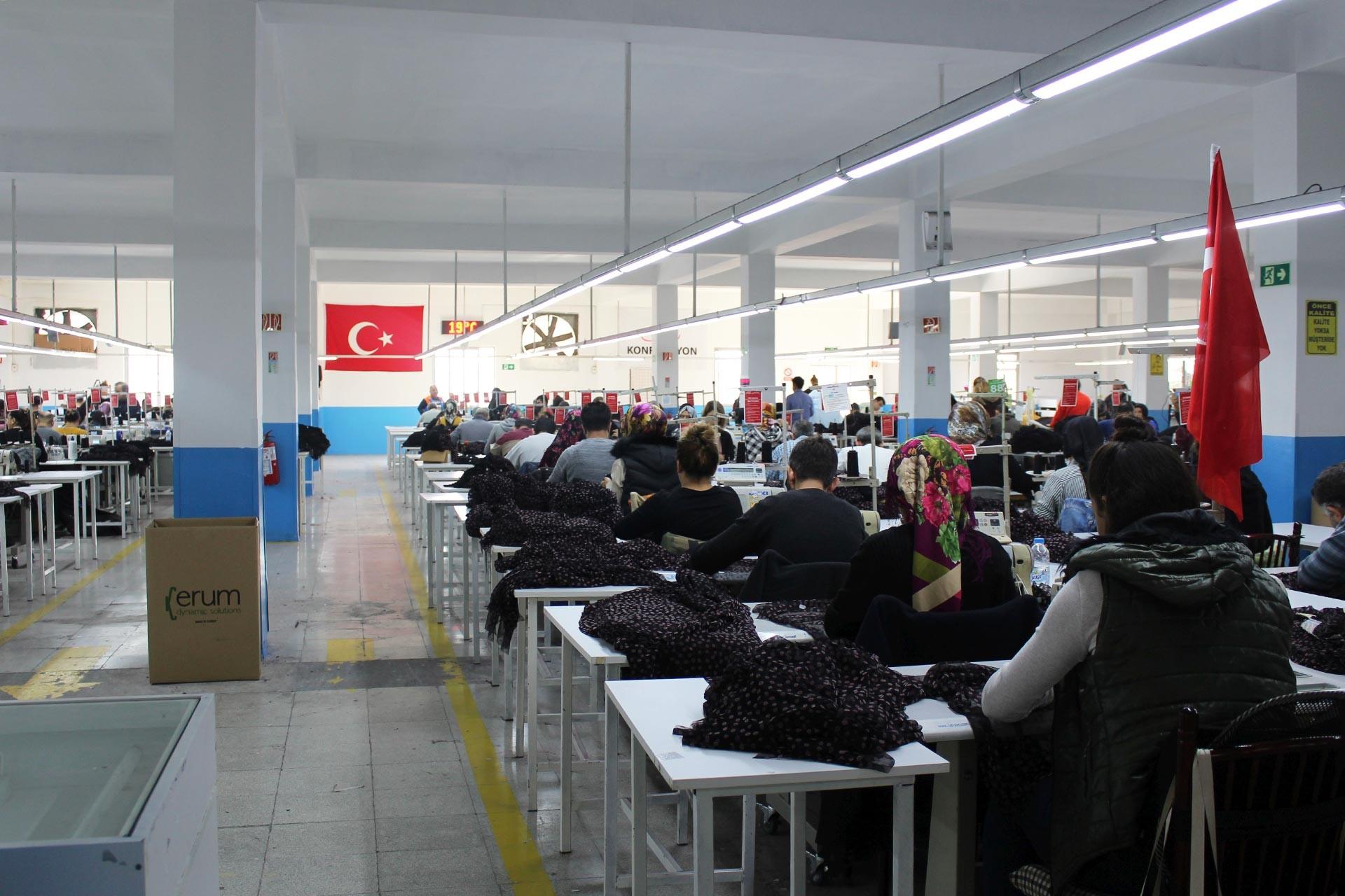 Tekstil atölyesinde işçiler sıra sıra dizilmiş halde çalışırken. İşçilerin çalışıtığı salonun büyük duvarında Türk Bayrağı asılı