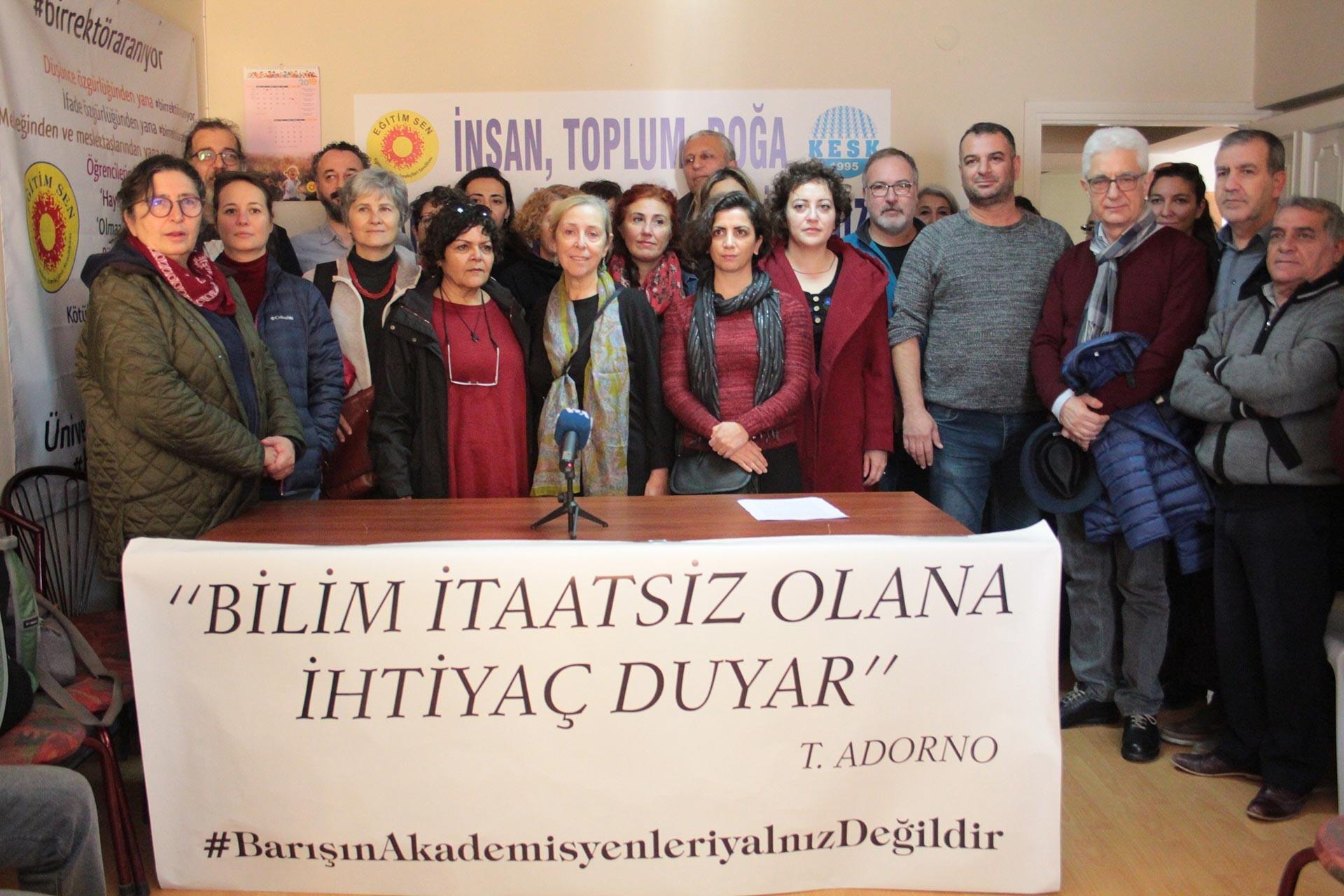 İzmir'de açıklama yapan Barış Akademisyenleri 'Bilim itaatsiz olana ihtiyaç duyar' yazılı pankartın arkasında dururken
