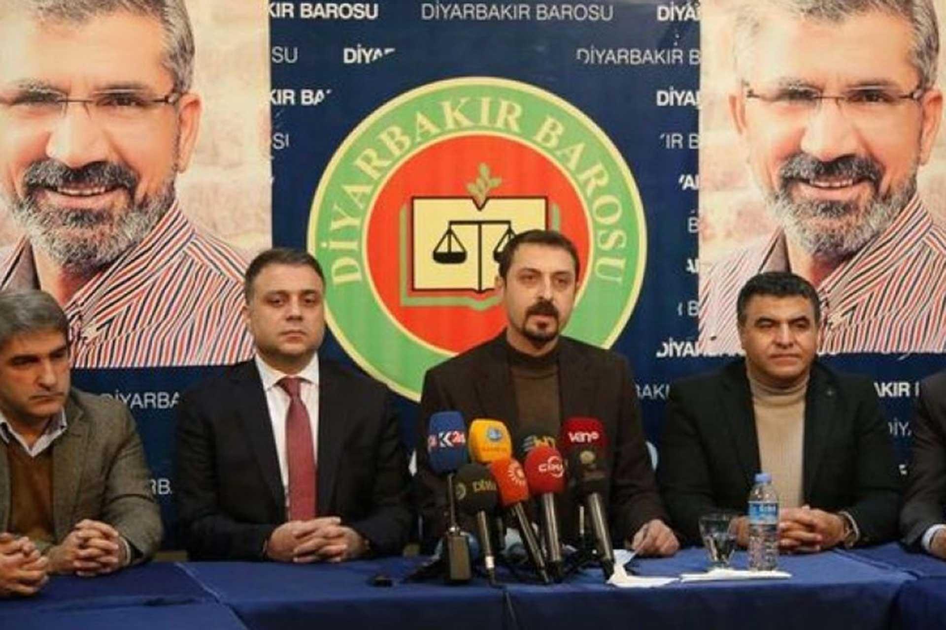 Diyarbakır Barosu yönetimi, Tahir Elçi'nin olduğu fotoğraflarının önüne kurulmuş bir masada basın açıklaması yapıyor.