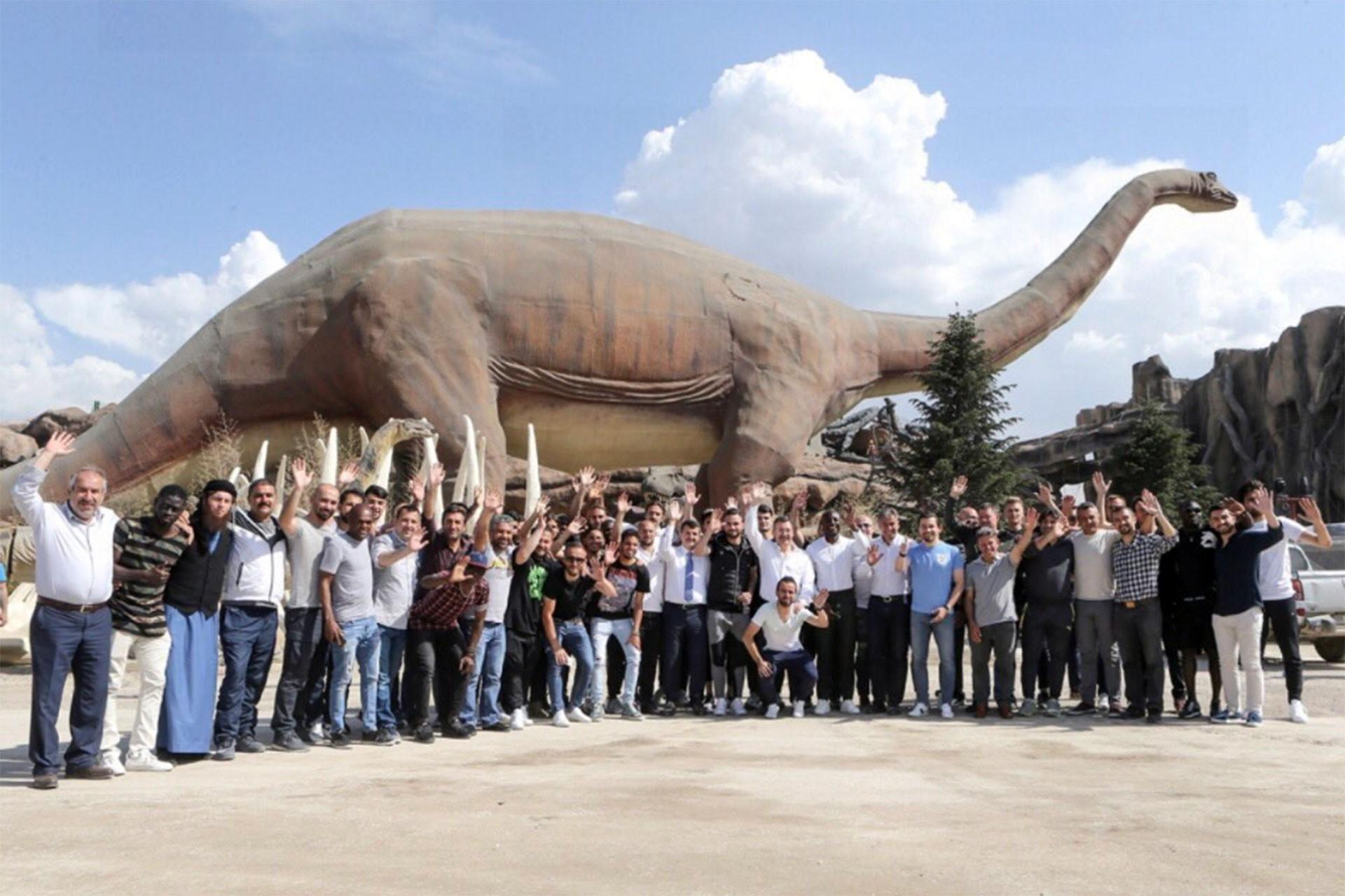 Melih Gökçek, dinozor heykeli önünde poz verirken
