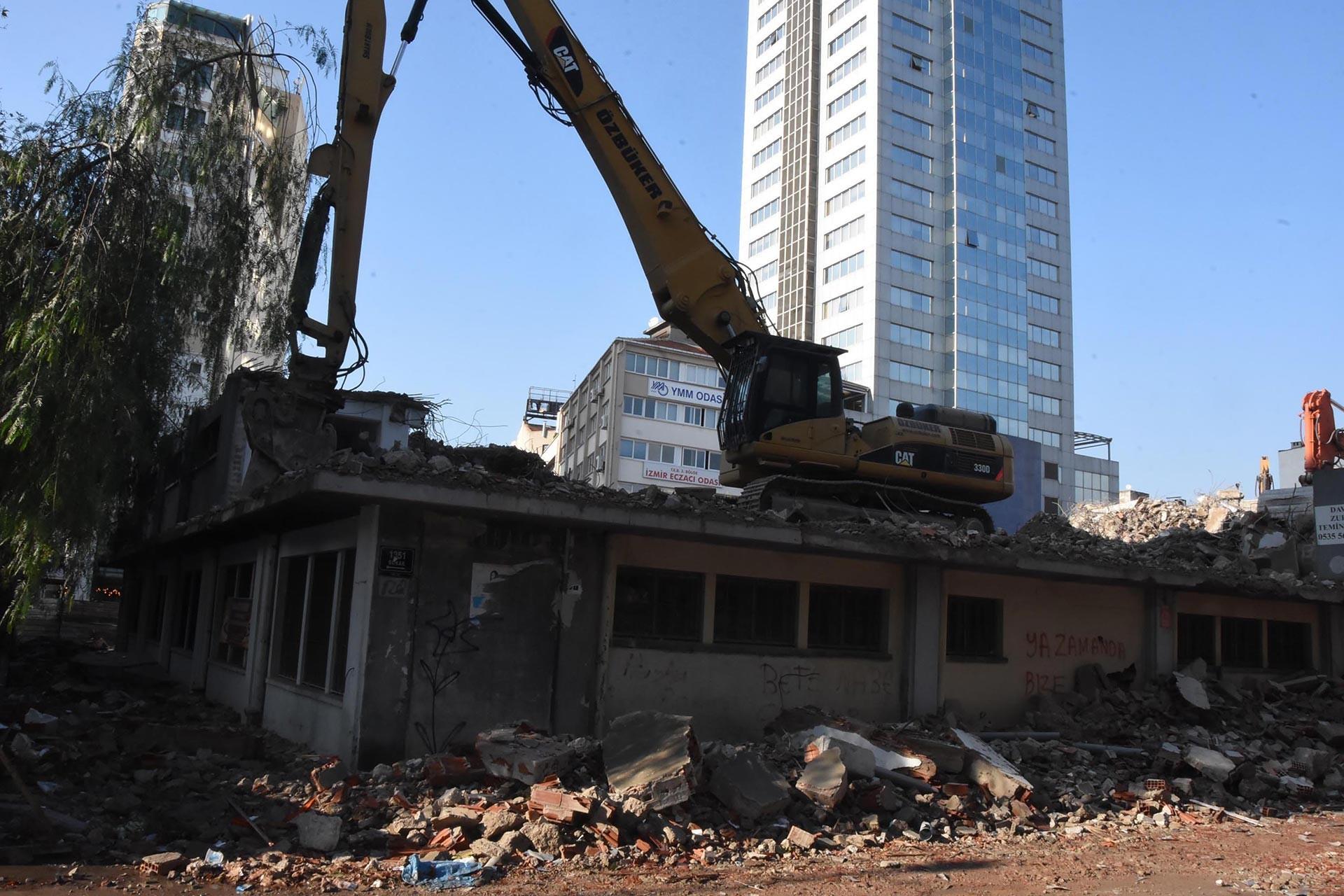 İş makinesi ile yıkılmakta olan bir gecekondu ve arkasında gözüken bir gökdelen