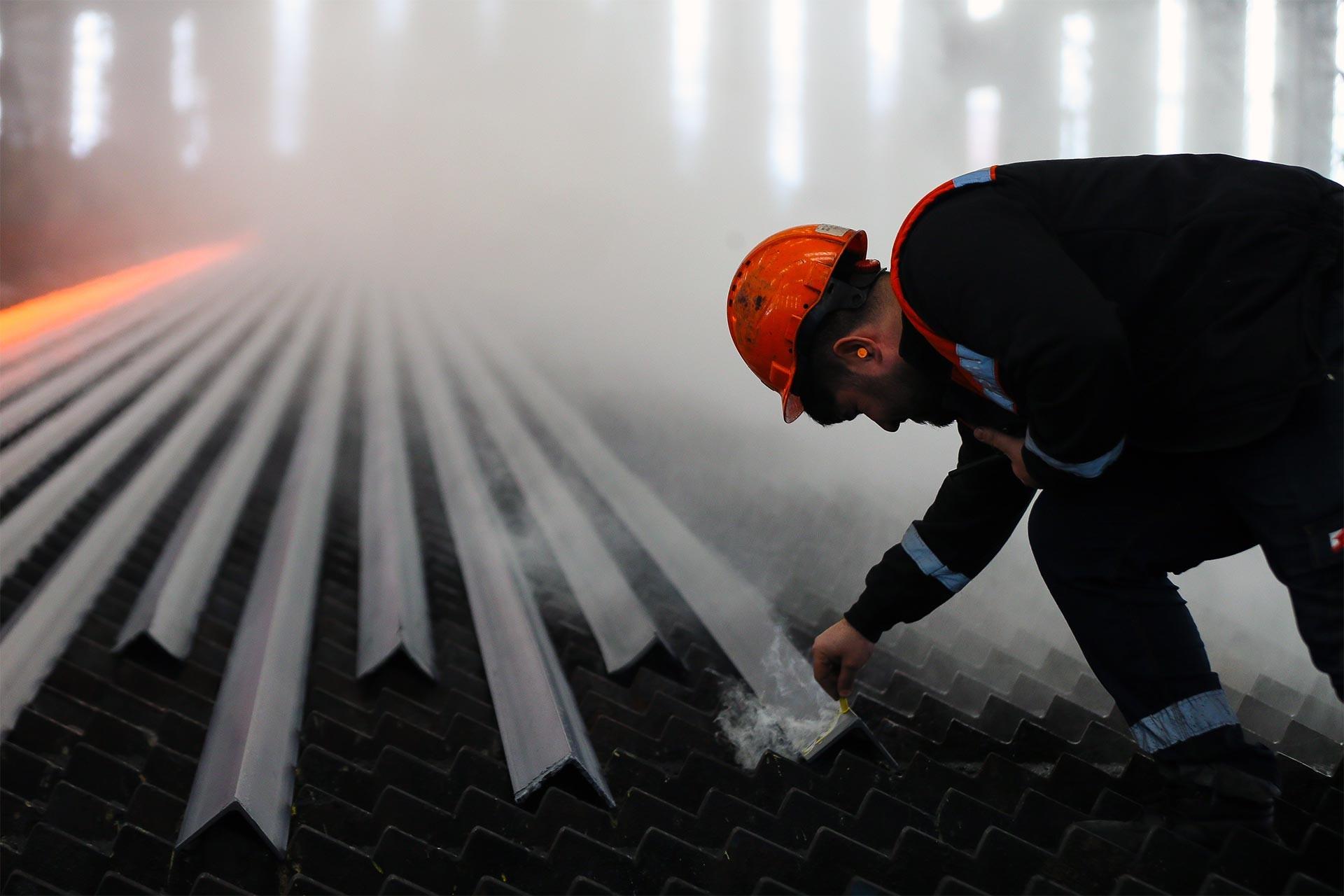 Demir-çelik fabrikası haddehanesinde çelik profilleri kontrol eden işçi
