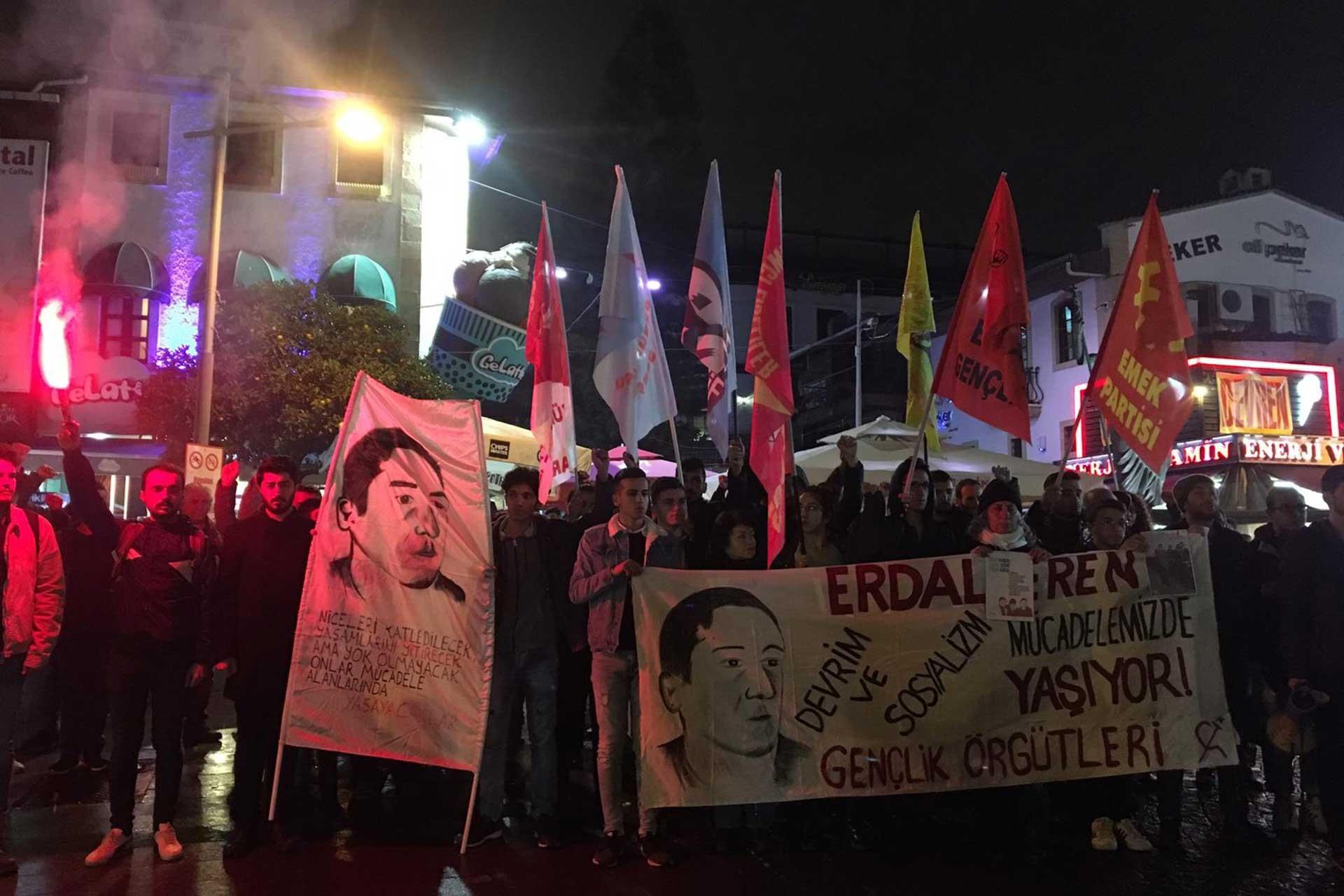 Erdal Eren pankartı arkasında, ellerinde meşale taşıyan gençler.
