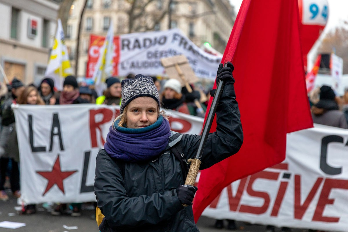 Emeklilik reformuna karşı yapılan eylemde pankartı tutan çok sayıda kişi yer aldı. Önde ise kızıl bayrak taşıyan biri bulunuyor.