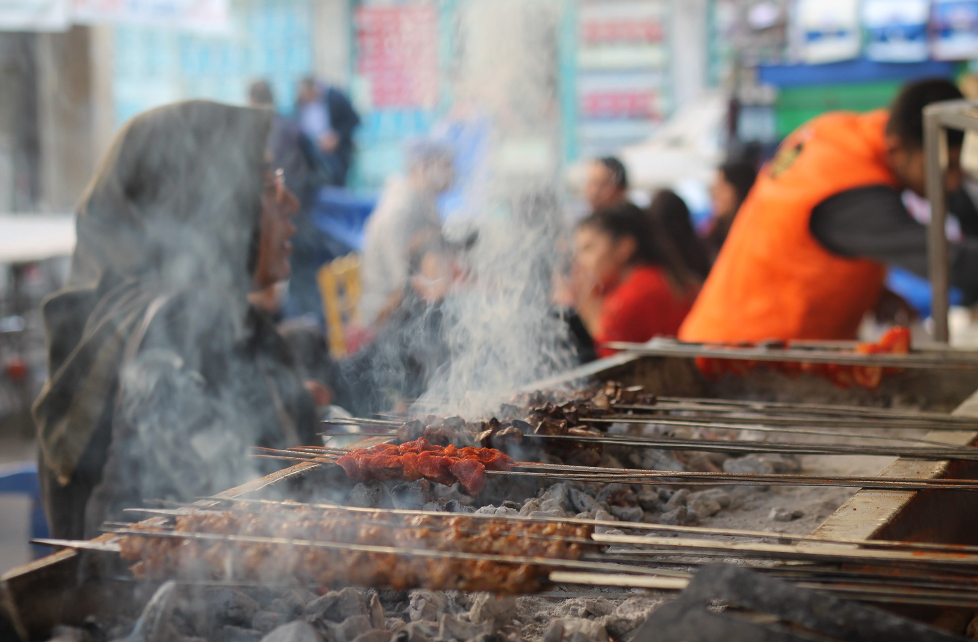 Kebapçıda mangal üzerinde pişen kebaplar ve müşteriler.