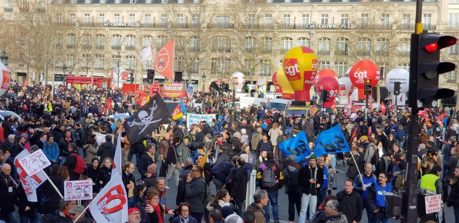 Çok sayıda kişi ellerinde dövizlerle emeklilik reformunu protesto ediyor. Alandaki balon ve bayraklar renkli görüntüler oluşturuyor.