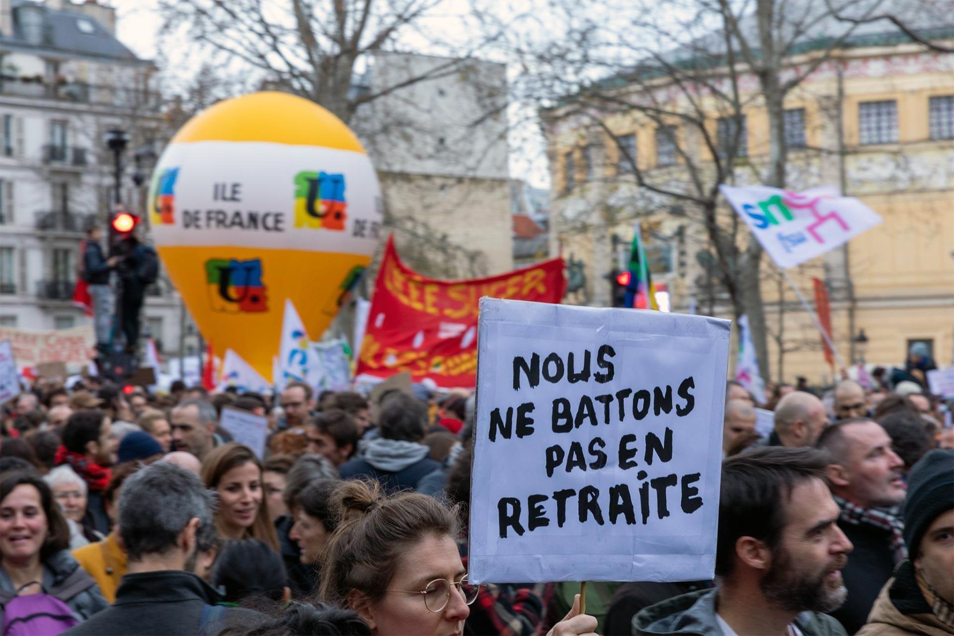 Fransa'da grev üzerine yürüyüş yapan kitle ve taşınan bir döviz