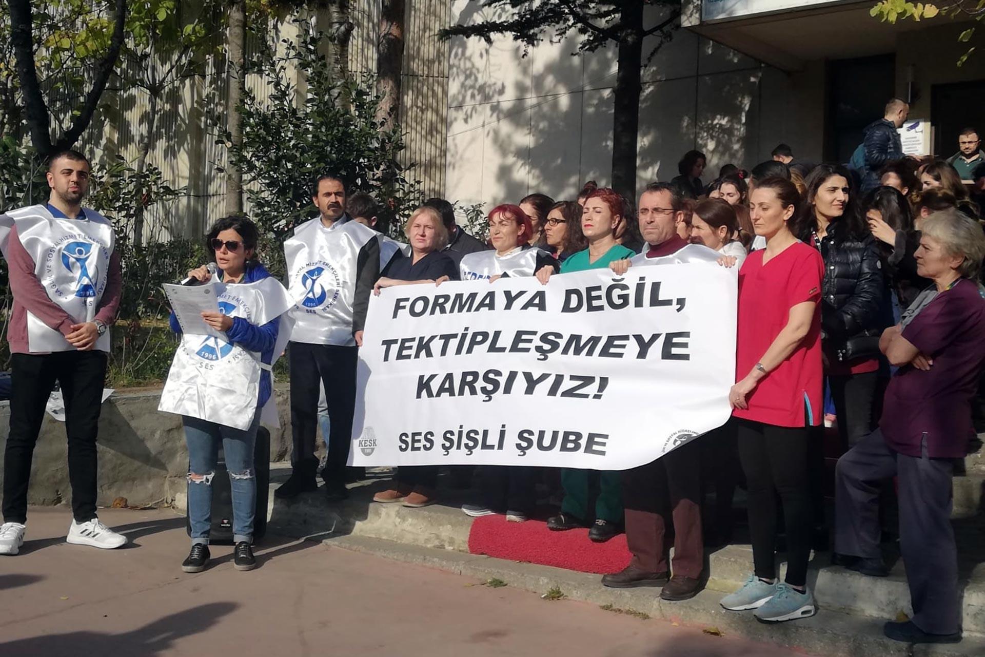 SES Şişli Şubesi üyesi sağlık emekçileri, İstanbul İl Sağlık Müdürlüğünün tek tip forma dayatmasına karşı 'Formaya değil tek tipleşmeye karşıyız' yazılı pankartla açıklama yaparken