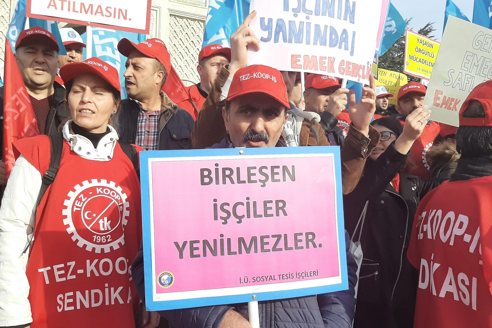 İstanbul Üniversitesi Beyazıt Kampüsü girişinde yapılan eylemde 'Birleşen işçiler yenilmezler' yazılı döviz tutan bir işçi