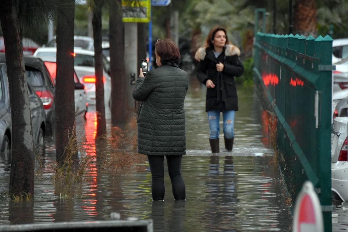 Su basan yolda dizlerine kadar suların içinde yürümeye çalışan iki kadın.