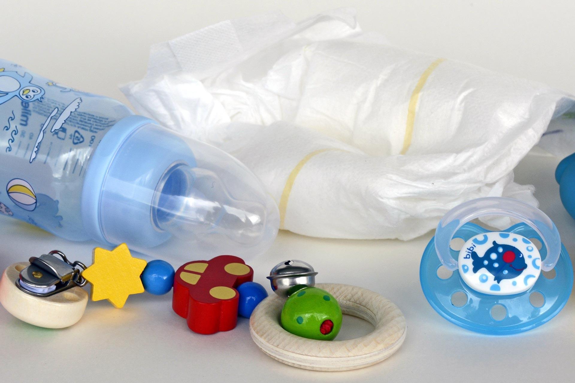 Bebek bezi, biberon, emzik ve bebek oyuncaklarının bir masada yan yana durduğu bir fotoğraf