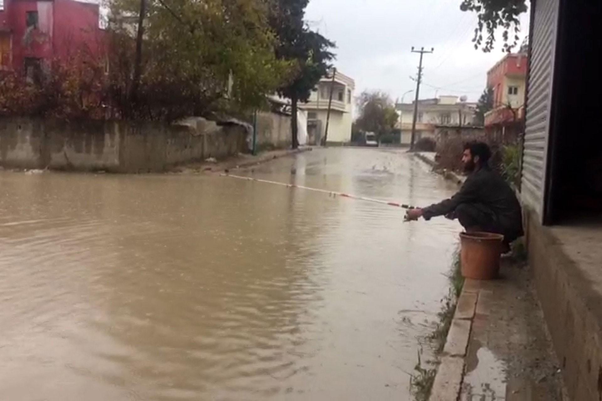 Mersin'de bir yurttaş su basan yolda olta attı