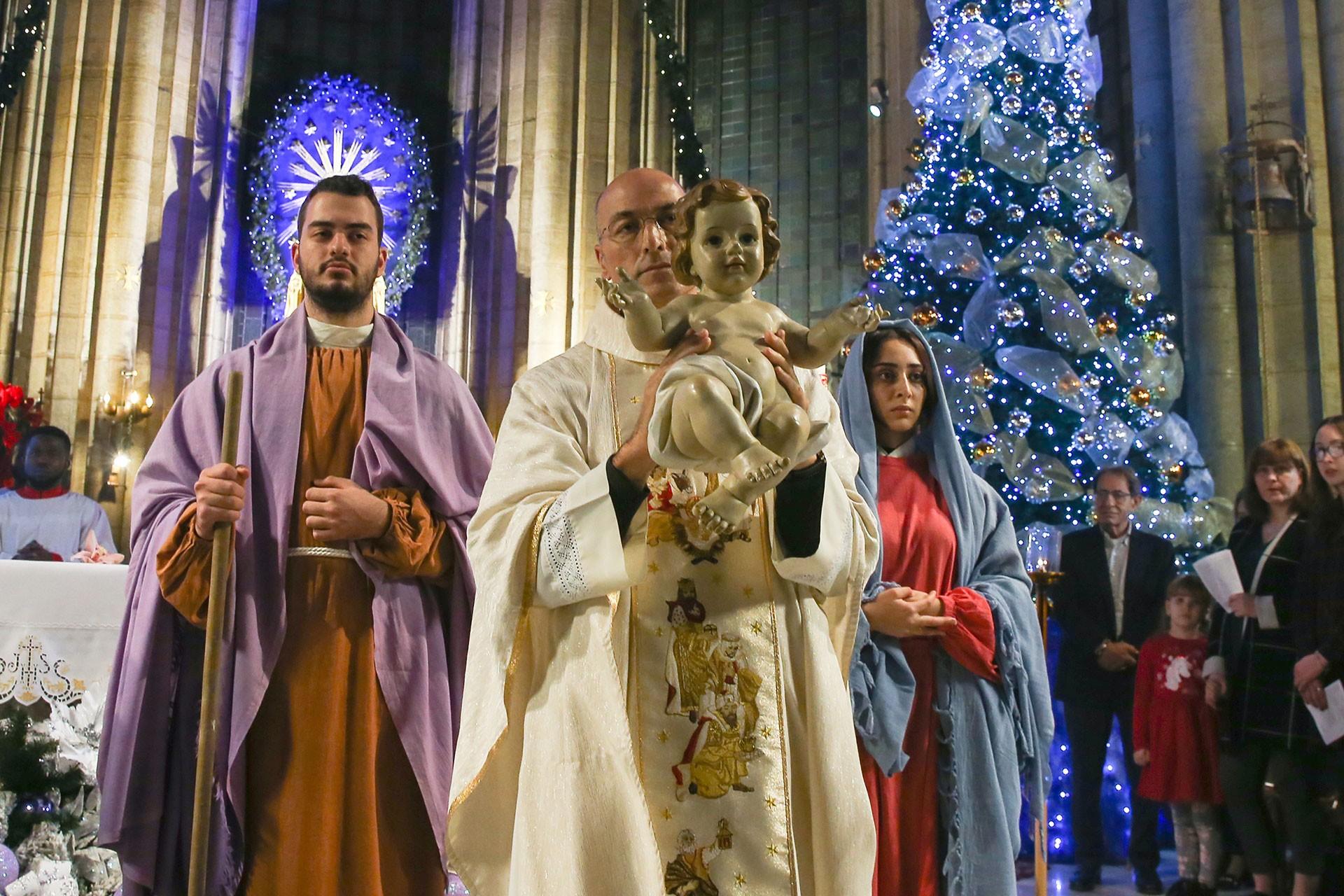 Saint Antuan Kilisesi'nde rahip elinde İsa'yı sembolize eden bebek heykeli tutuyor. Yanıbaşında genç bir erkek ve genç bir kadın var.