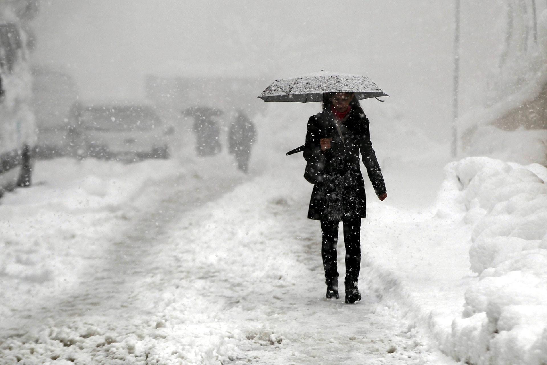 Hakkari'de kar yağışı nedeniyle karla kaplı yollar ve karda yürümeye çalışan bir kadın.