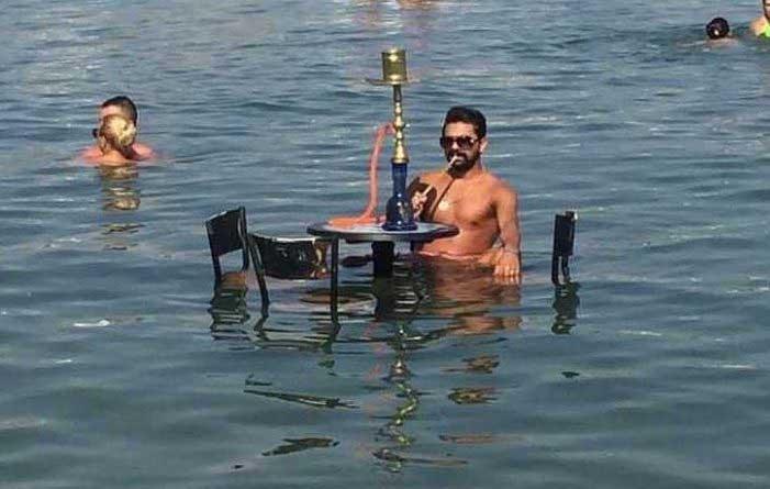 Erzin Soylu, denizde nargile içiyor.