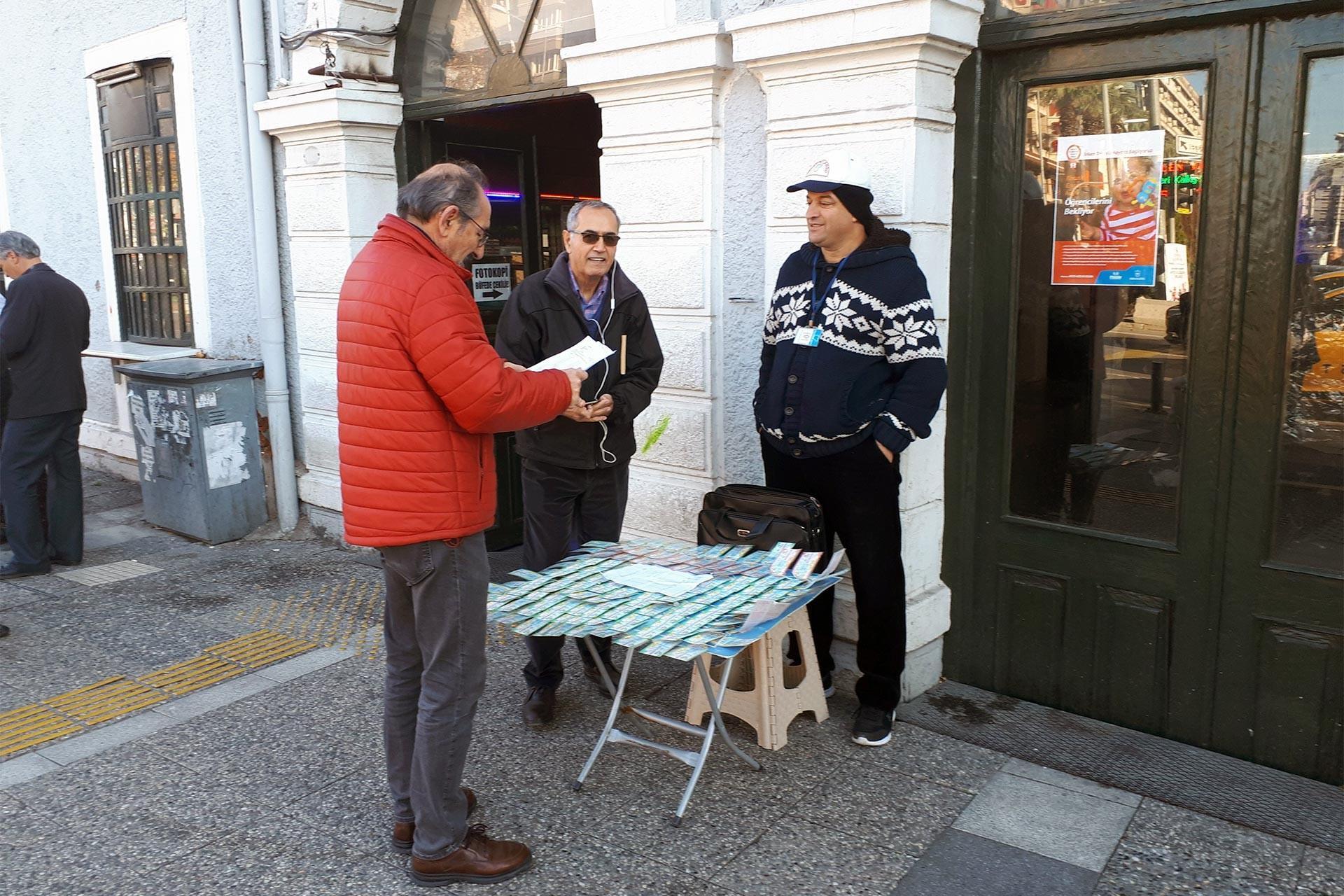 Milli Piyango satıcısı ve tezgahı önünde bilet bakan bir kişi