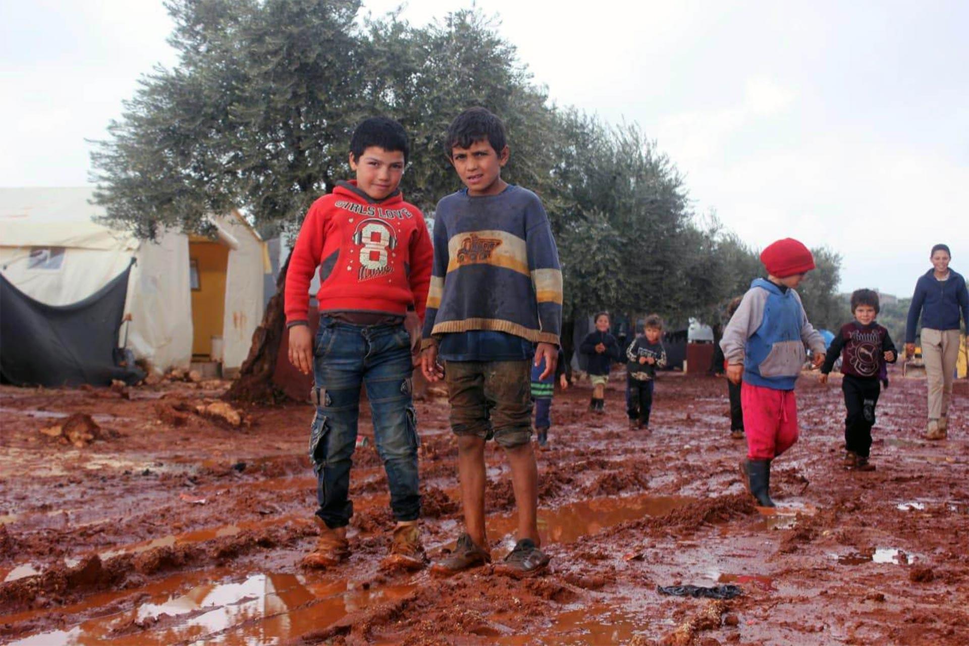 Ayakları çamur içerisinde kalmış mülteci çocuklar