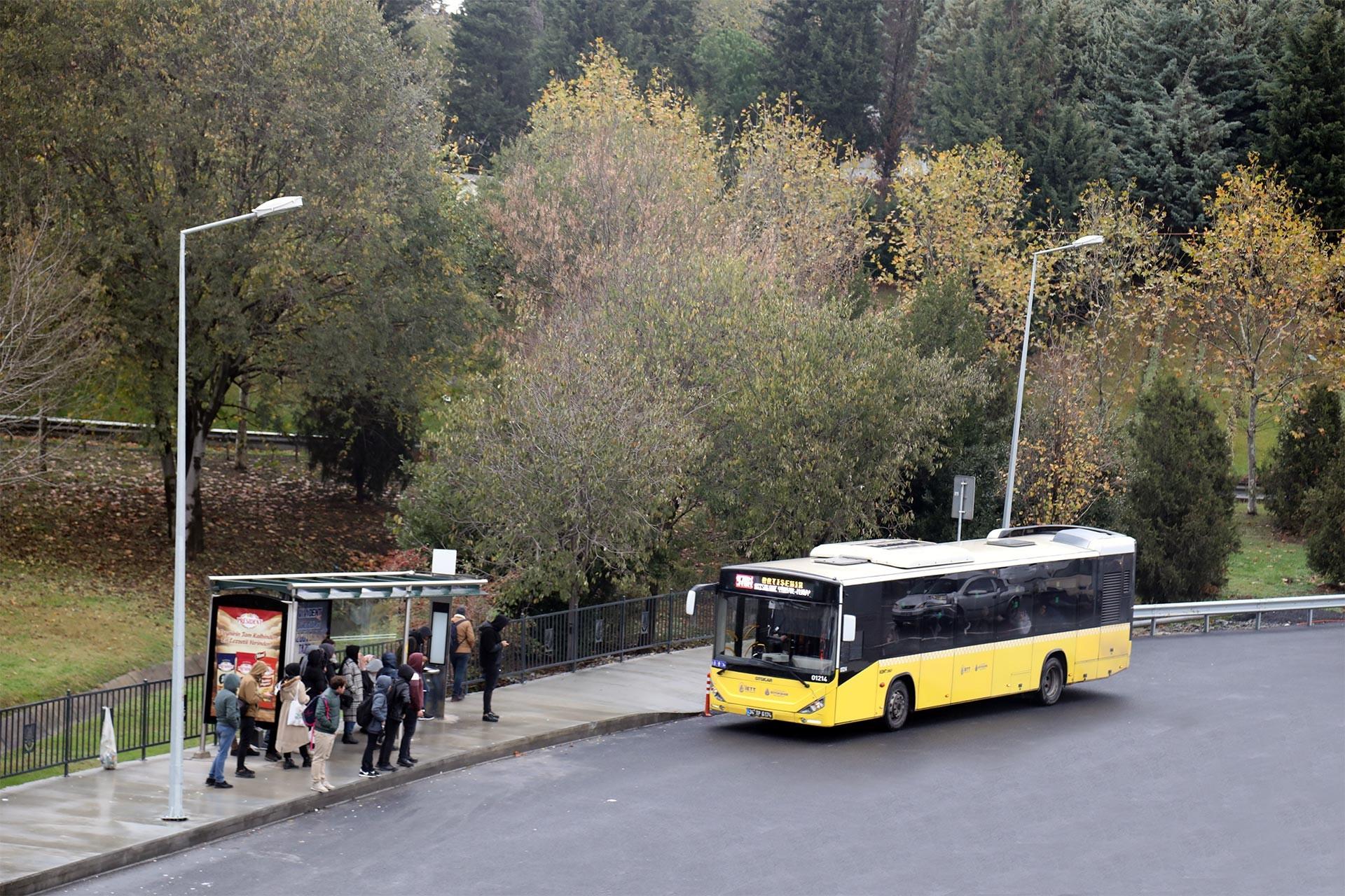 Durakta otobüsbekleyen yolcular ve durağa yanaşan İETT otobüsü