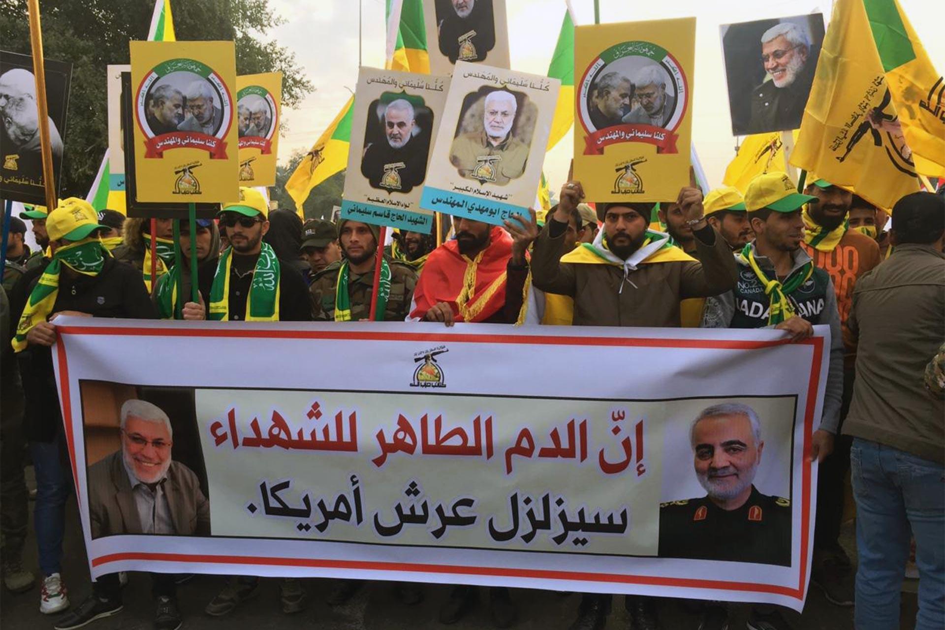 Süleymani ve Mühendis'in cenaze töreni için toplanan Iraklılar ellerinde döviz ve bayraklar taşıyor