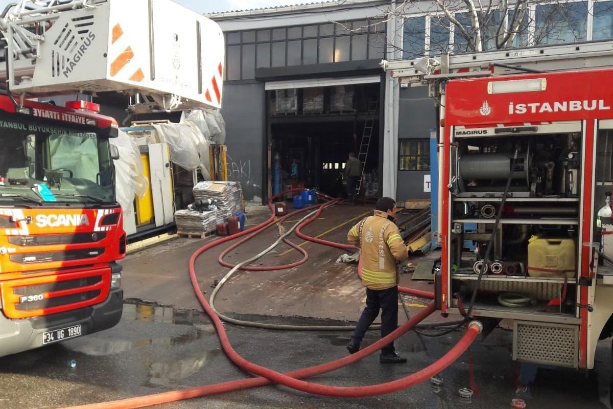 İşyerinde çıkan ve söndürülen yangının ardından soğutma çalışmaları yapan itfaiyeciler.