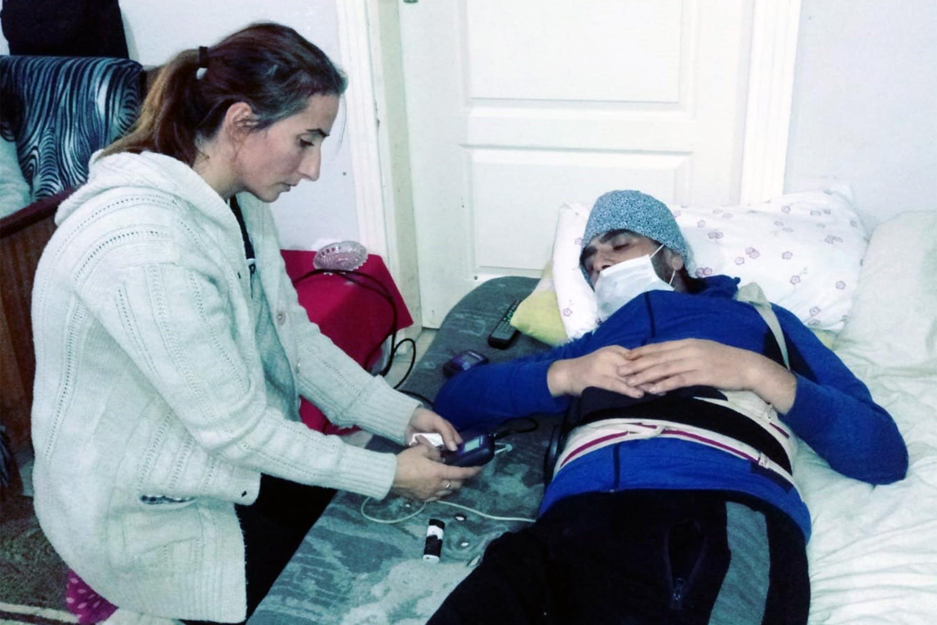 Diyabet nedeniyle engelli hale gelen hasta yatakta muayene edilirken
